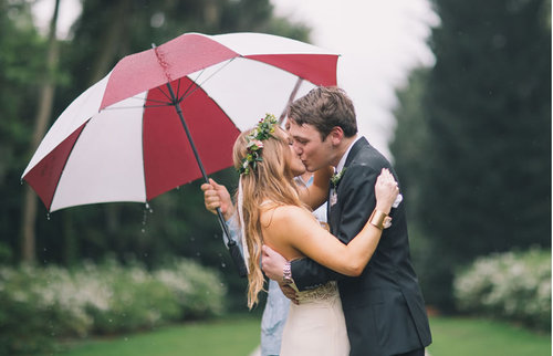 Engaged couple kissing in rain